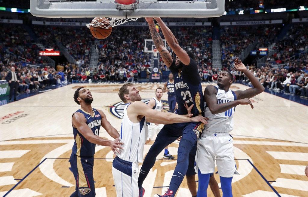 New Orleans Pelicans forward Anthony Davis (23) dunks over Dallas Mavericks forwards Dorian Finney-Smith (10) and Dirk Nowitzki during the first half ...