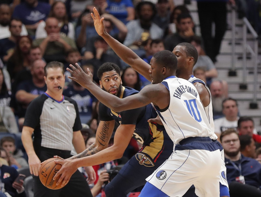 New Orleans Pelicans forward Anthony Davis looks to pass the ball past Dallas Mavericks forward Dorian Finney-Smith (10) during the first half of an N...