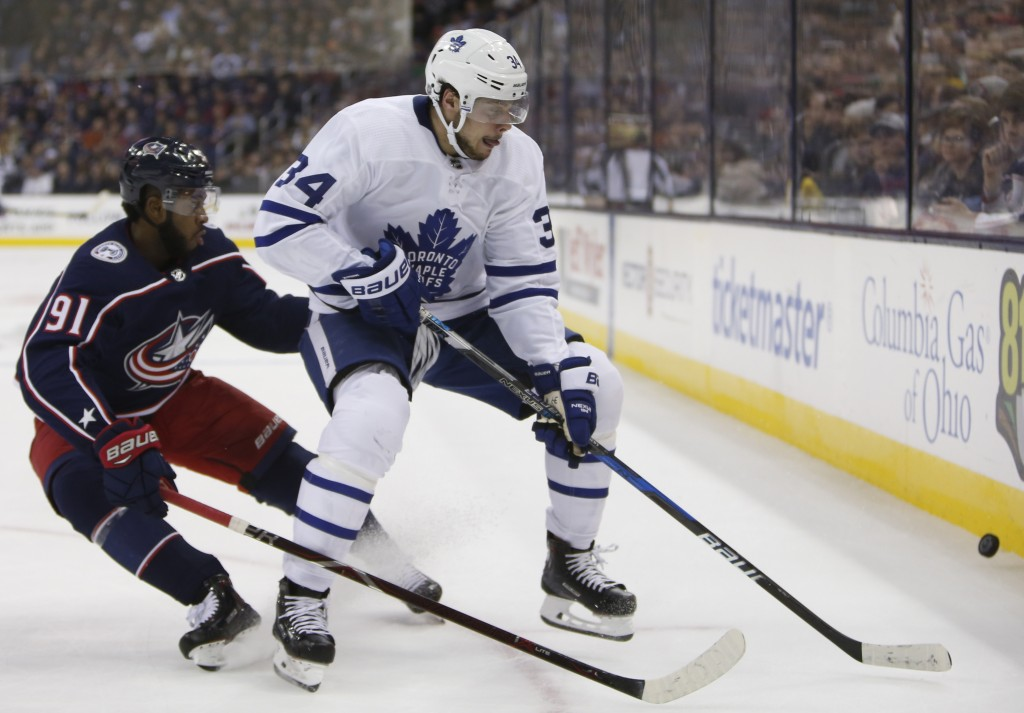 Toronto Maple Leafs' Auston Matthews, right, keeps the puck away from Columbus Blue Jackets' Anthony Duclair during the first period of an NHL hockey ...
