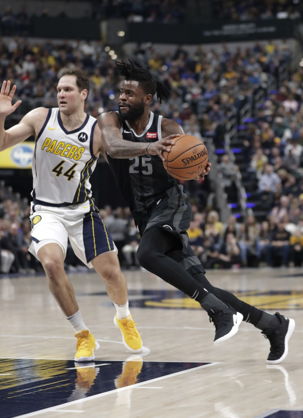 Detroit Pistons guard Reggie Bullock (25) drives on Indiana Pacers forward Bojan Bogdanovic (44) during the first half of an NBA basketball game in In...