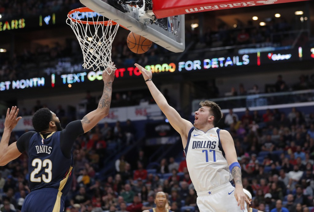 Dallas Mavericks forward Luka Doncic (77) goes to the basket against New Orleans Pelicans forward Anthony Davis (23) during the first half of an NBA b...