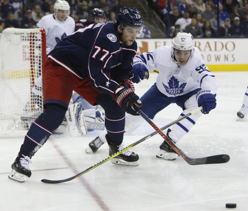Columbus Blue Jackets' Josh Anderson, left, looks for an open pass as Toronto Maple Leafs' Igor Ozhiganov, of Russia, defends during the second period...