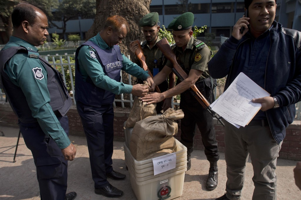 Bangladeshi police personnel seal the voting material at a distribution center before being transported to polling stations on the eve of the general ...