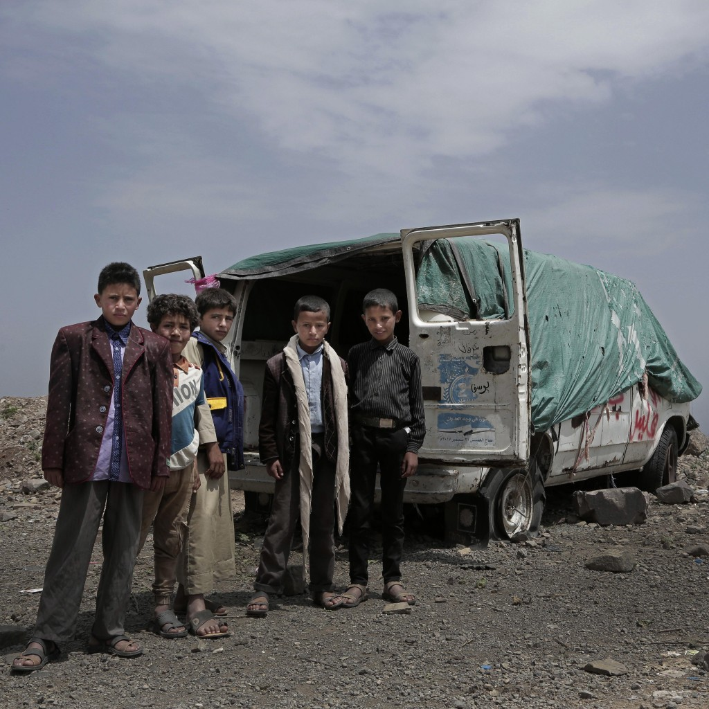 Boys stand next to the dilapidated remains of a van with four flat tires half-sunk in the dirt on a mountain in Ibb, Yemen on Aug. 3, 2018. (AP Photo/...