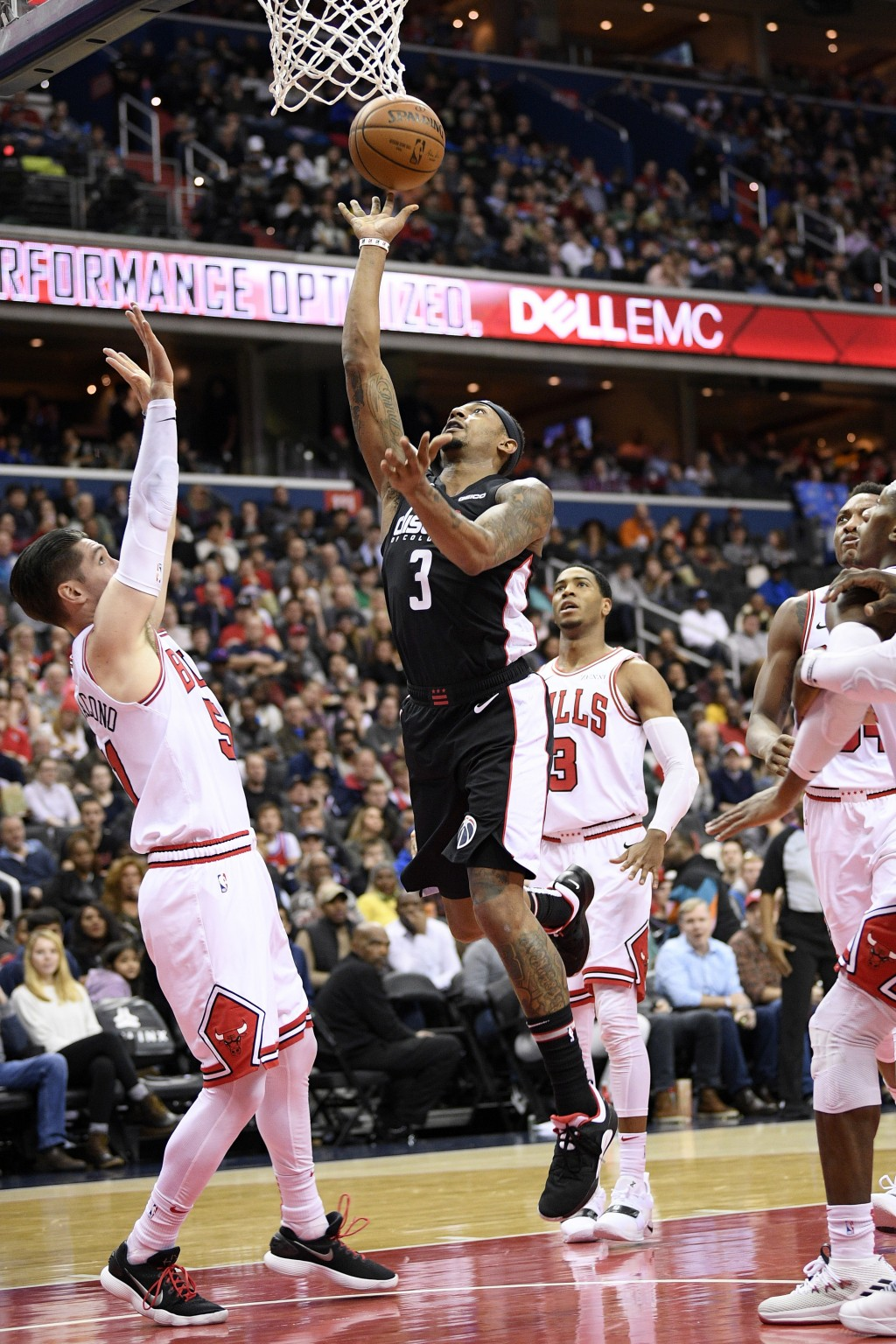 Washington Wizards guard Bradley Beal, center, goes to the basket against Chicago Bulls guard Ryan Arcidiacono (51) and guard Shaquille Harrison, back...