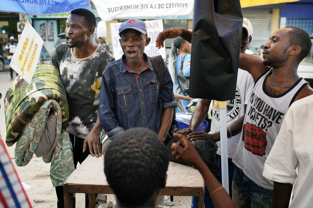 In this photograph taken Friday, Dec. 28, 2018, Kinshasa residents argue about politics at a streetside newsstand in Kinshasa, Congo. Congolese people...