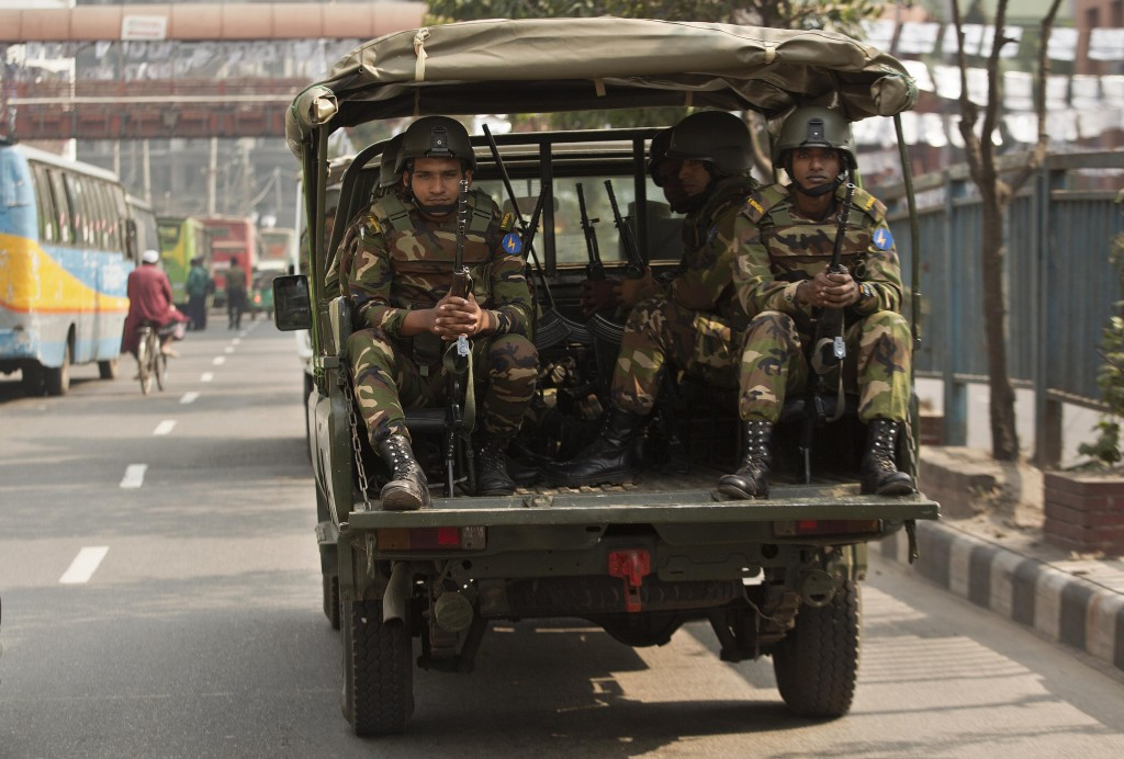 Bangladeshi army soldiers sit inside a vehicle as they patrol the streets on the eve of the general elections in Dhaka, Bangladesh, Saturday, Dec. 29,...