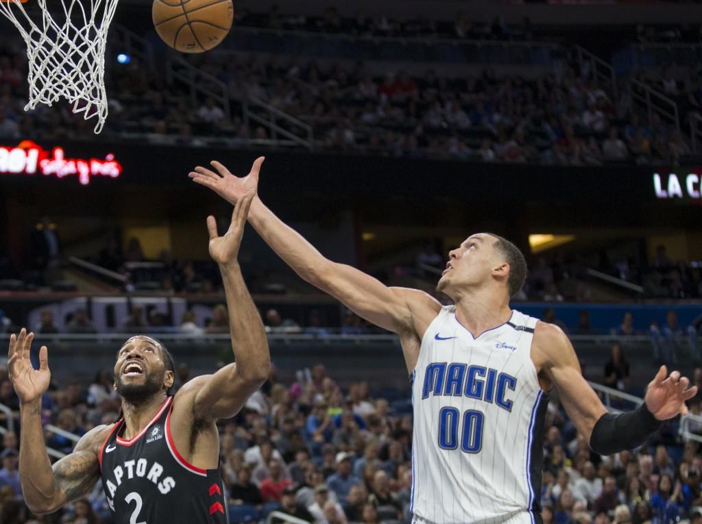 Toronto Raptors forward Kawhi Leonard (2) and Orlando Magic forward Aaron Gordon (00) go up for the rebound during the second half of an NBA basketbal...