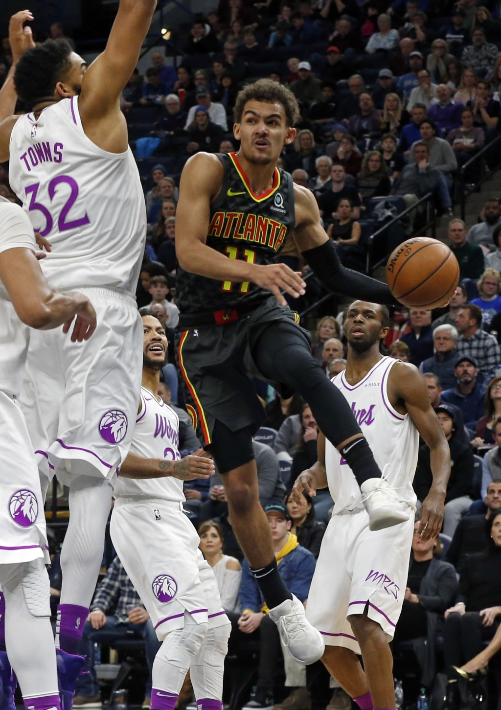 Atlanta Hawks' Trae Young, right, goes to the air to make a pass as Minnesota Timberwolves' Karl-Anthony Towns defends during the second half of an NB...