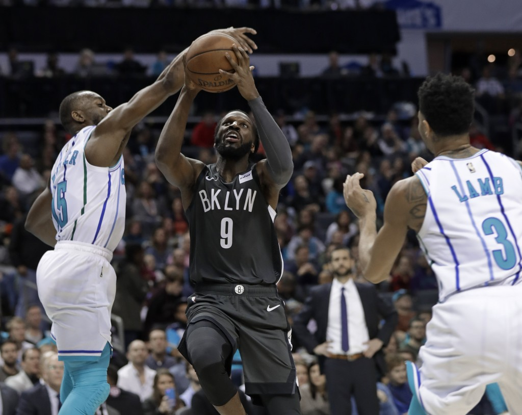 Brooklyn Nets' DeMarre Carroll (9) is fouled as he drives between Charlotte Hornets' Kemba Walker (15) and Jeremy Lamb (3) during the first half of an...