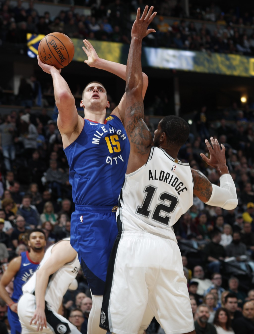 Denver Nuggets center Nikola Jokic, back, goes up for a basket over San Antonio Spurs forward LaMarcus Aldridge in the first half of an NBA basketball...