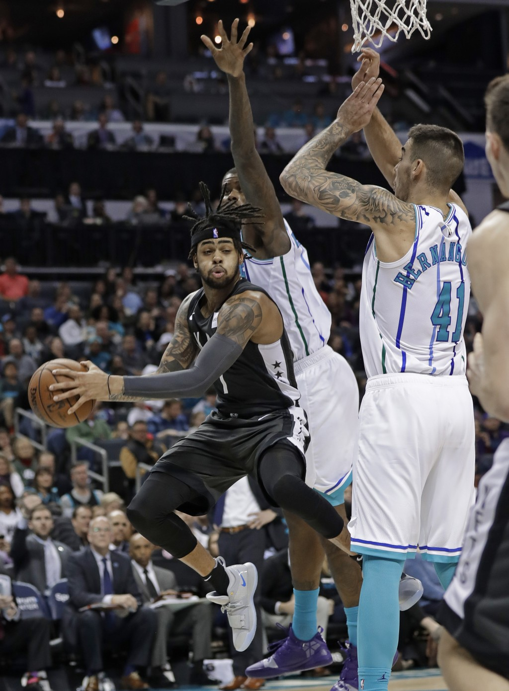Brooklyn Nets' D'Angelo Russell (1) drives between Charlotte Hornets' Willy Hernangomez (41) and Marvin Williams during the first half of an NBA baske...