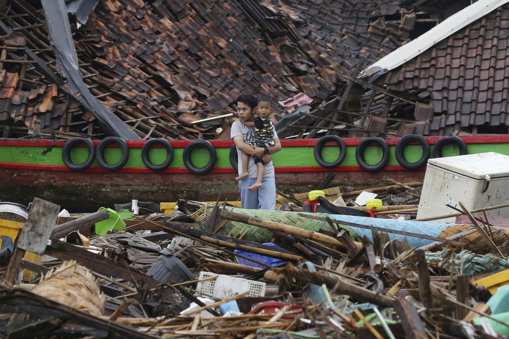 A man holds a child as he surveys the damage at a village struck by a tsunami in Sumur, Indonesia, Tuesday, Dec. 25, 2018. The waves struck without wa