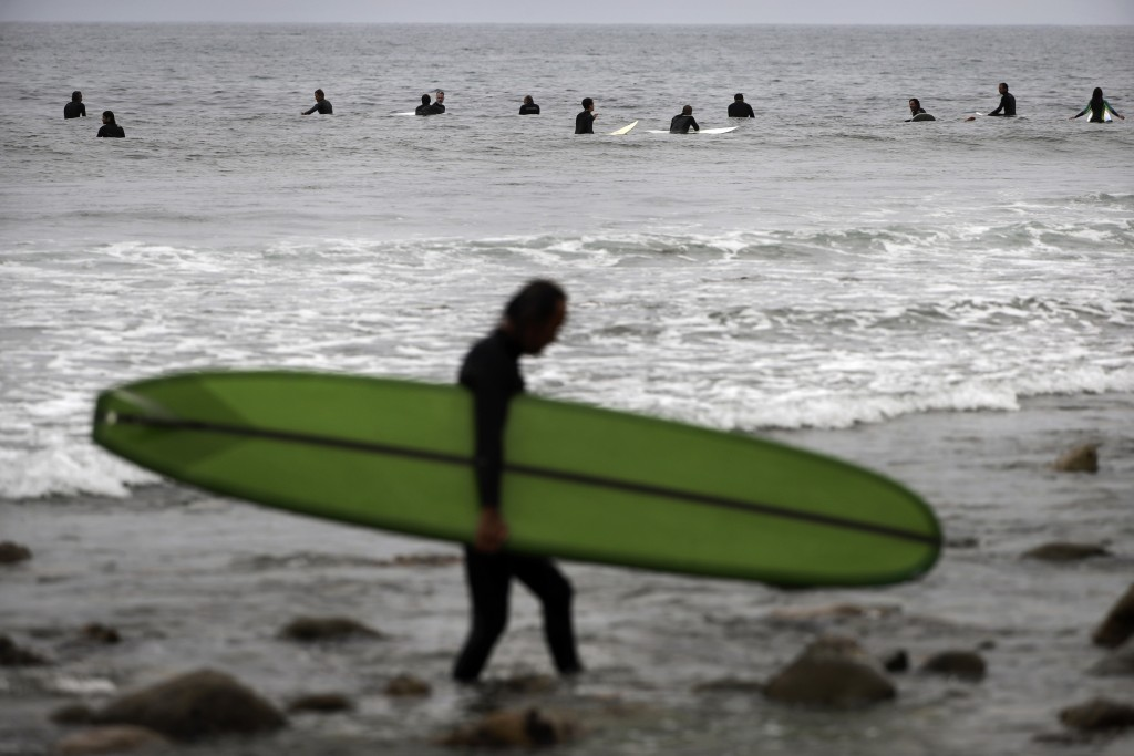 FILE - In this Sept. 12, 2016, file photo, Hiroshi Konishi, foreground, walks out of the ocean after surfing as other surfers wait for waves in Malibu...