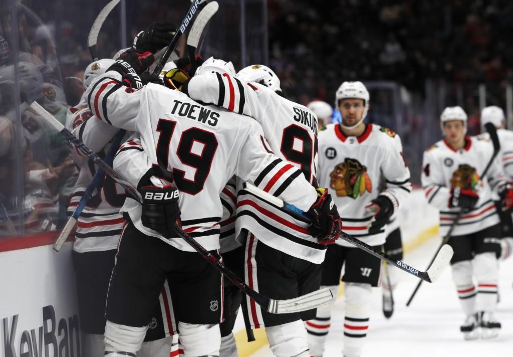 Chicago Blackhawks right wing Patrick Kane is enveloped by teammates, including Jonathan Toews and Dylan Sikura, after Kane scored in overtime of an N...
