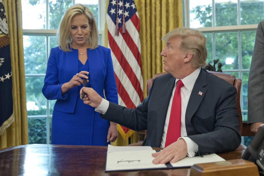 FILE - In this Wednesday, June 20, 2018 file photo, President Donald Trump gives the pen he used to sign the executive order to end family separations...