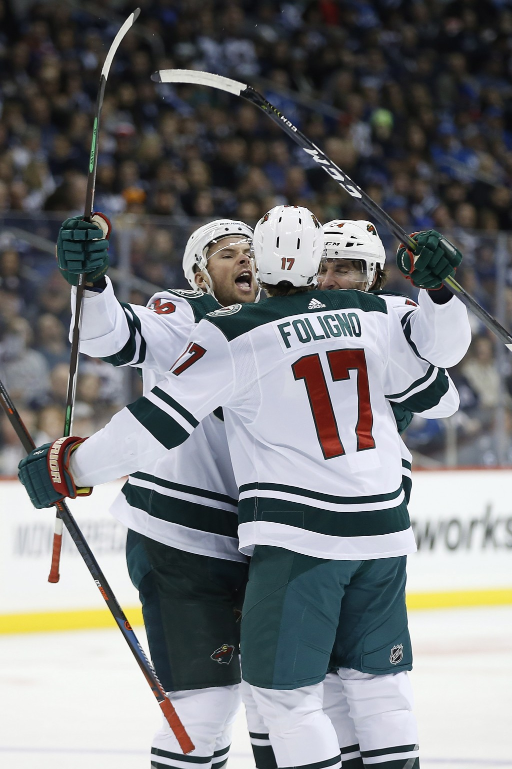 Minnesota Wild's Nate Prosser (39), Marcus Foligno (17) and Matt Bartkowski (44) celebrate Bartkowski's goal against the Winnipeg Jets during first pe...