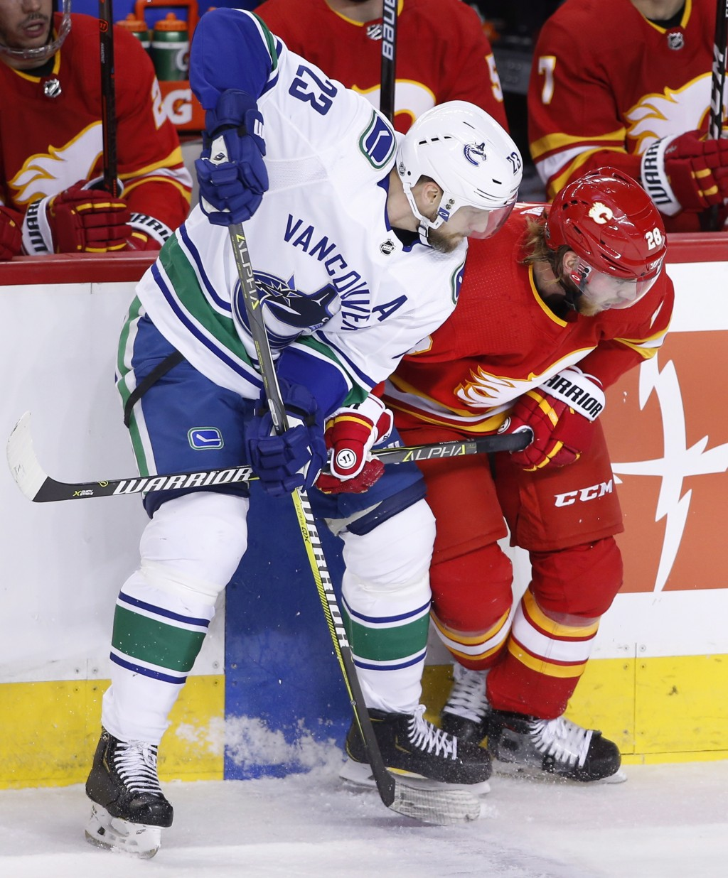 Vancouver Canucks' Alexander Edler, left, from Sweden, battles with Calgary Flames' Elias Lindholm, from Sweden, during the first period of an NHL hoc...