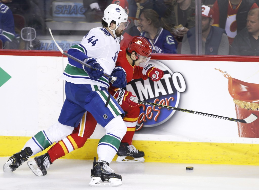 Vancouver Canucks' Erik Gudbranson, left, battles for the puck with Calgary Flames' Johnny Gaudreau during the first period of an NHL hockey game Satu...