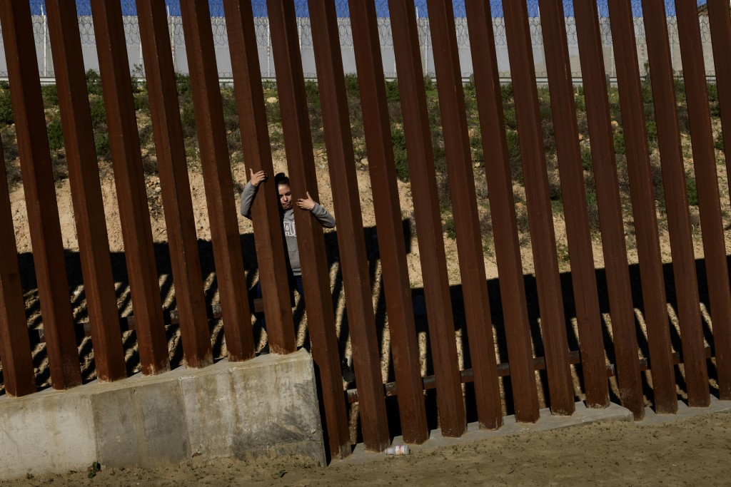 A migrant jumps the border fence to get into the U.S. side to San Diego, Calif., from Tijuana, Mexico, Saturday, Dec. 29, 2018. Discouraged by the lon...