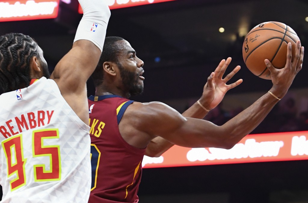 Cleveland Cavaliers guard Alec Burks, right, shoots as Atlanta Hawks forward DeAndre' Bembry (95) defends during the first half of an NBA basketball g...
