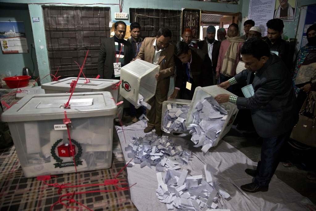 Bangladeshi polling officials empty the ballot boxes for counting after the voting ended at a polling station in the ancient city of Panam Nagar, abou...