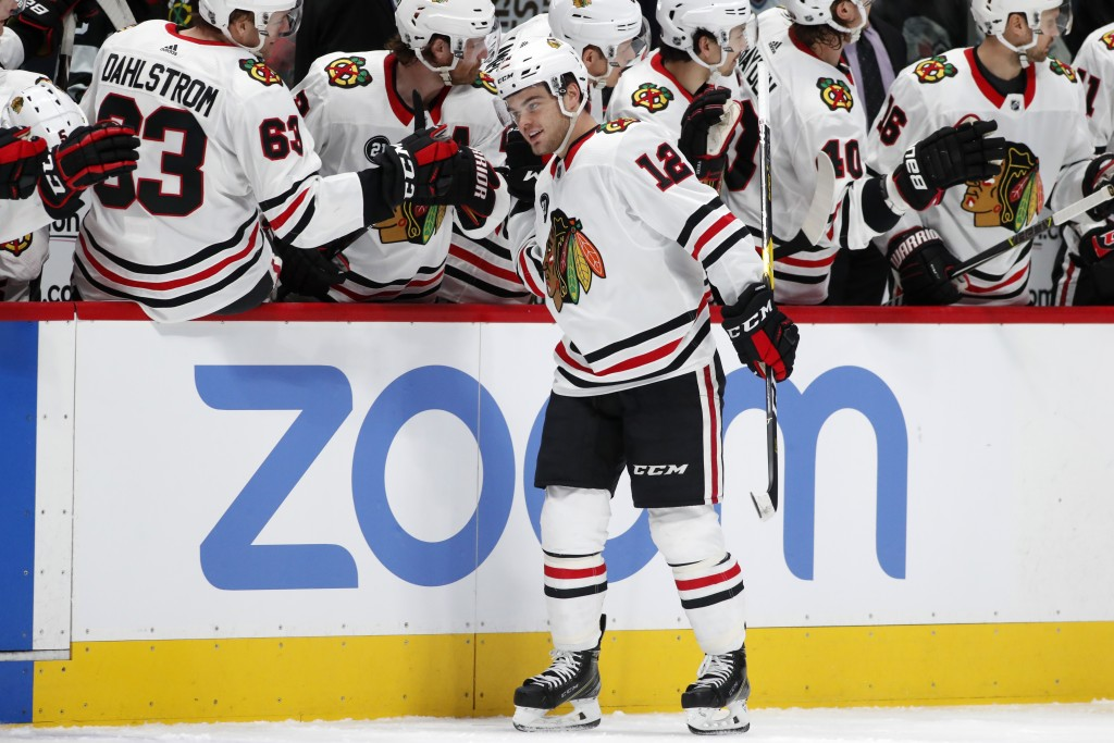 Chicago Blackhawks left wing Alex DeBrincat, front, is congratulated as he passes the team box after scoring a goal against the Colorado Avalanche in ...