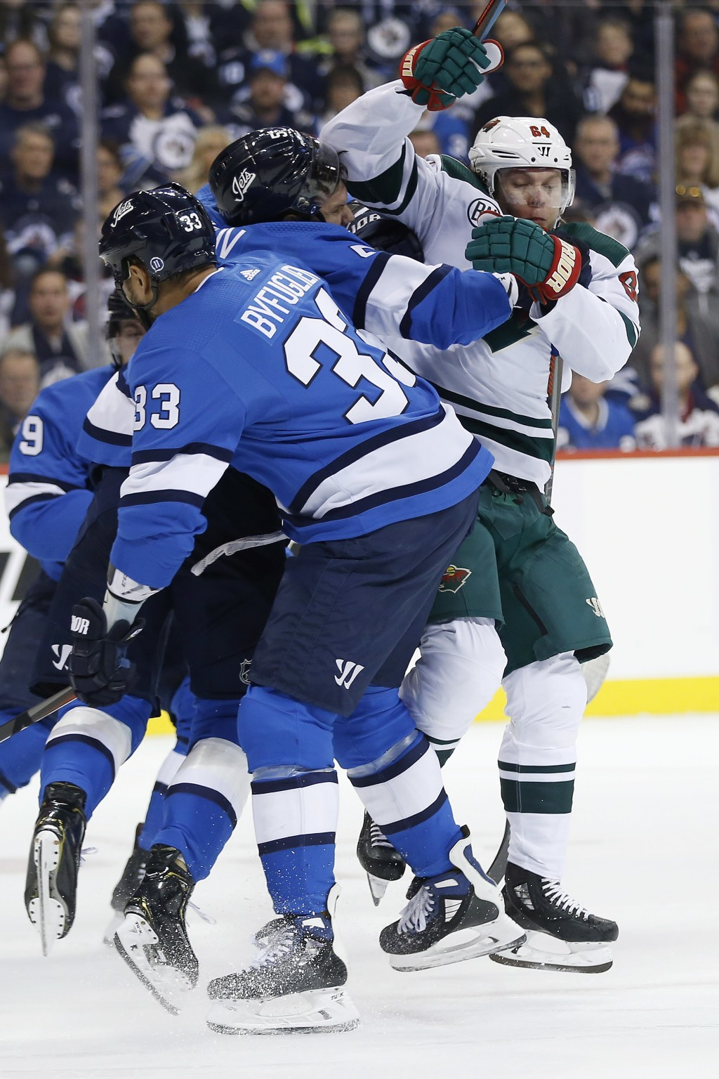 Winnipeg Jets' Dustin Byfuglien (33) and Dmitry Kulikov (5) defend against Minnesota Wild's Mikael Granlund (64) during first period NHL action in Win...