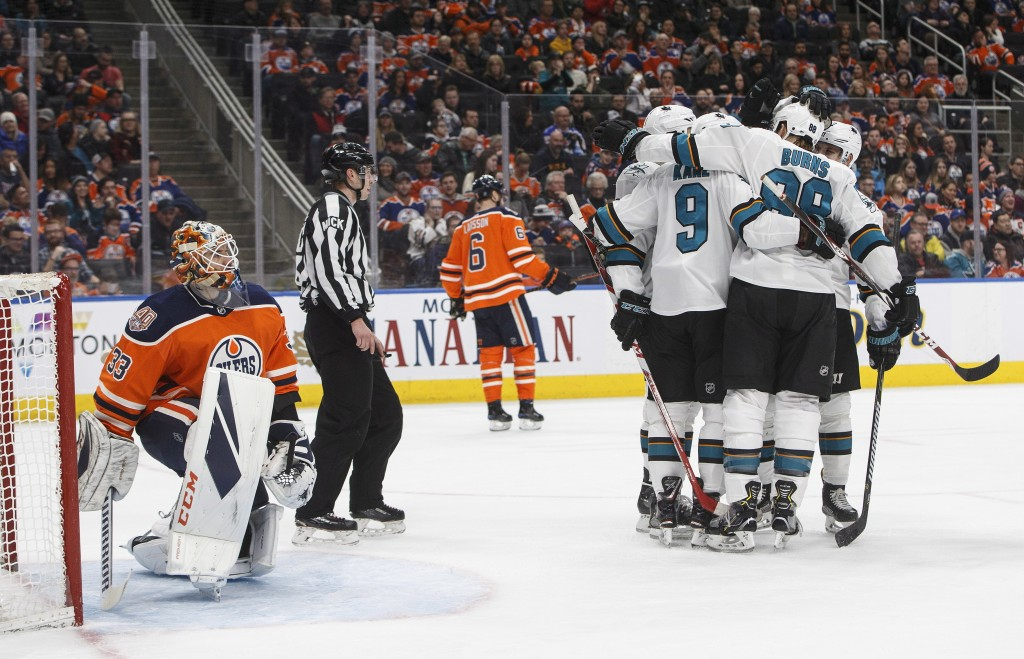 San Jose Sharks players Including Evander Kane (9) and Brent Burns (88) celebrate a goal as Edmonton Oilers' goalie Cam Talbot (33) looks on during th...