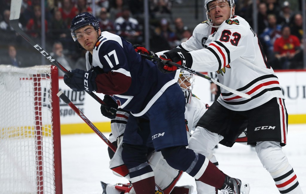 Chicago Blackhawks defenseman Carl Dahlstrom, right, clears Colorado Avalanche center Tyson Jost out from in front of the net in the first period of a...