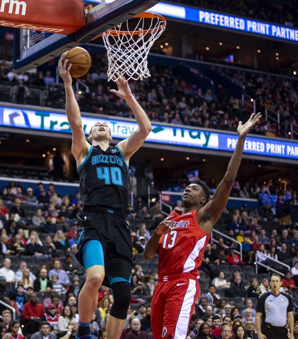 Charlotte Hornets center Cody Zeller (40) makes a layup past Washington Wizards center Thomas Bryant (13) during the first half of an NBA basketball g...