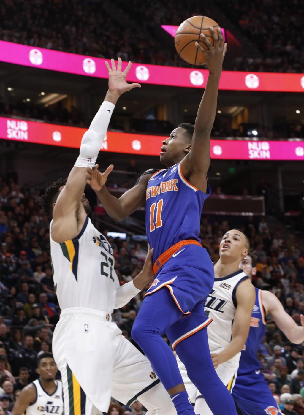 New York Knicks' Frank Ntilikina (11) attempts a layup as Utah Jazz's Thabo Sefolosha, left, defends in the first half of an NBA basketball game on Sa...