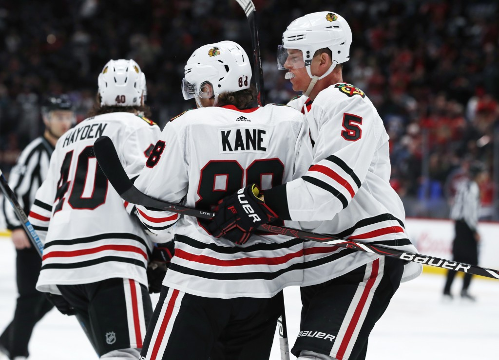 Chicago Blackhawks defenseman Connor Murphy, right, hugs right wing Patrick Kane, who scored against the Colorado Avalanche in overtime of an NHL hock...
