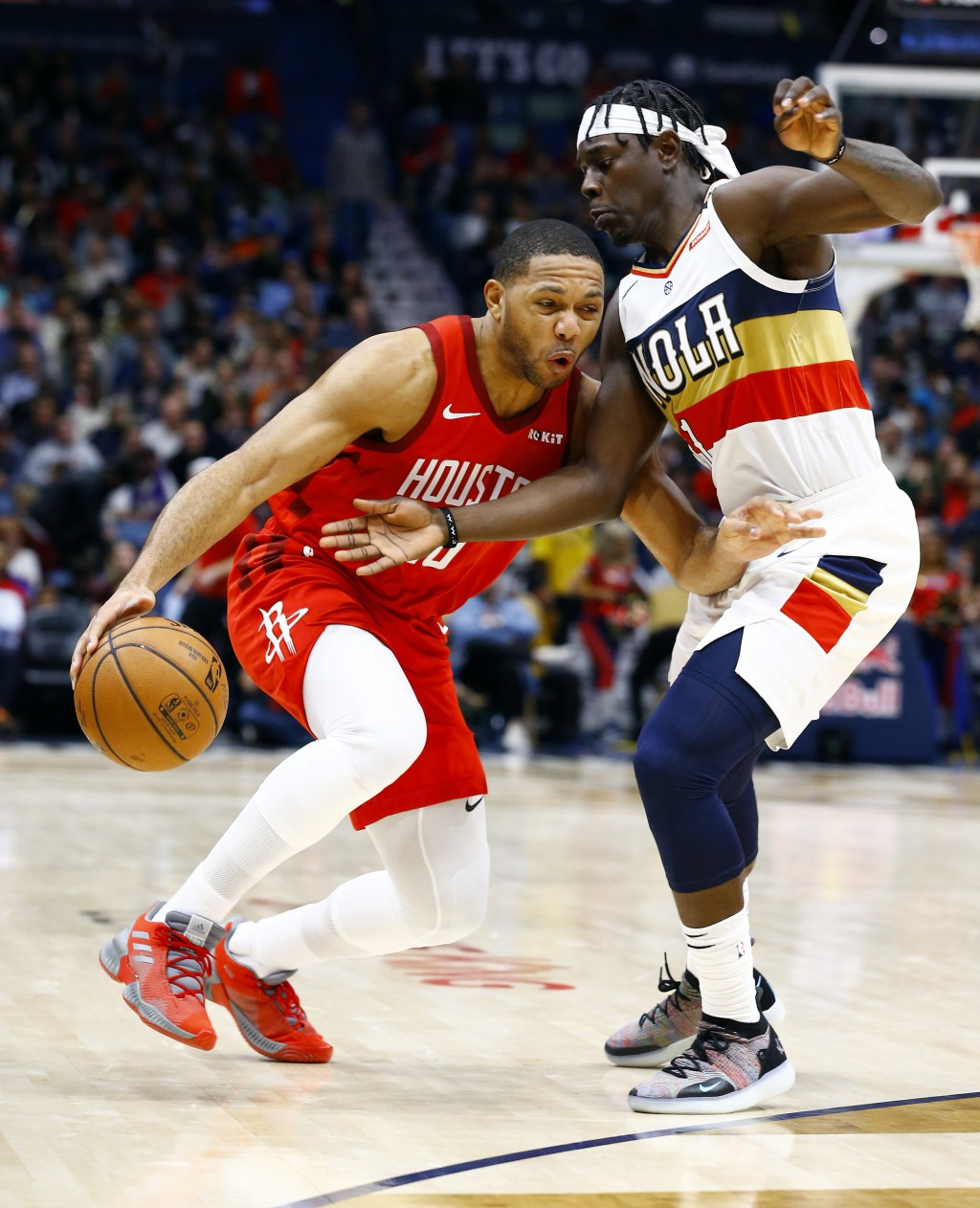 Houston Rockets guard Eric Gordon (10) drives to the basket around New Orleans Pelicans guard Jrue Holiday (11) during the first half of an NBA basket...