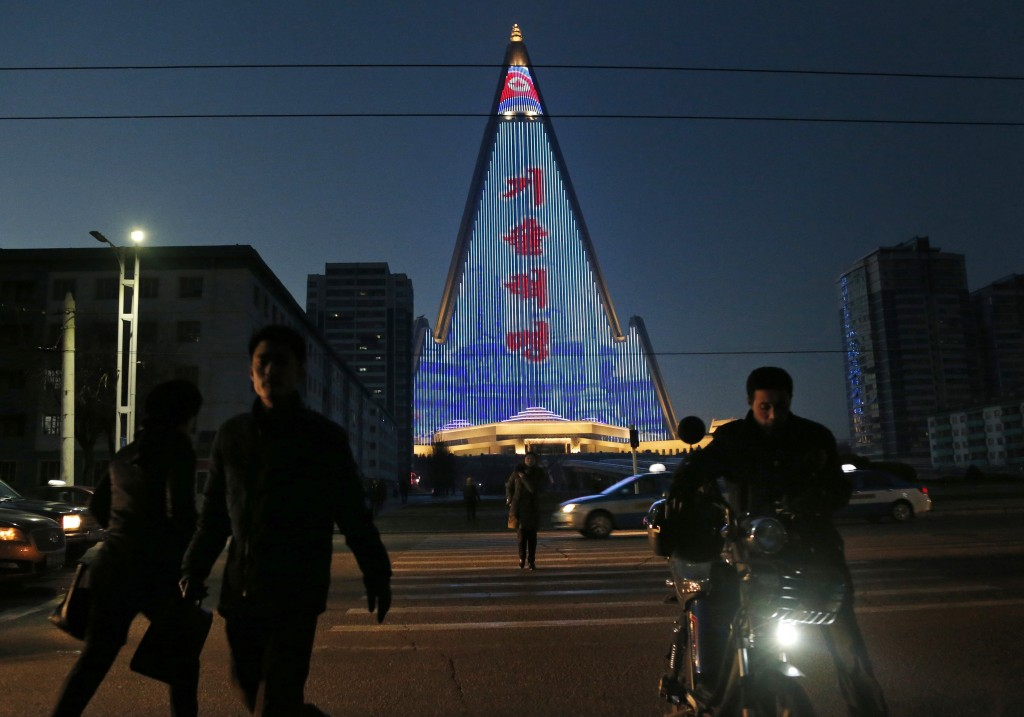 In this  Dec. 20, 2018 photo, people cross the street as a propaganda message is displayed on the facade of the pyramid-shaped Ryugyong Hotel in Pyong...