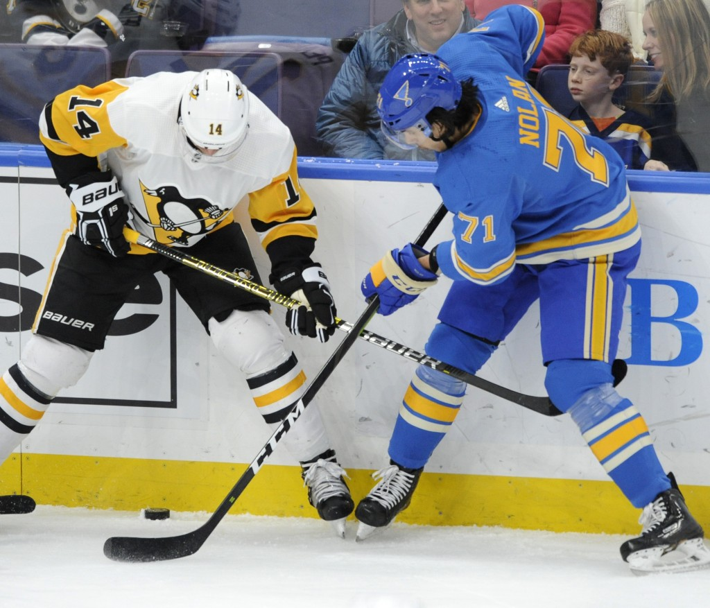 St. Louis Blues' Jordan Nolan (71) reaches for the puck with Pittsburgh Penguins' Tanner Pearson (14) during the first period of an NHL hockey game, S...