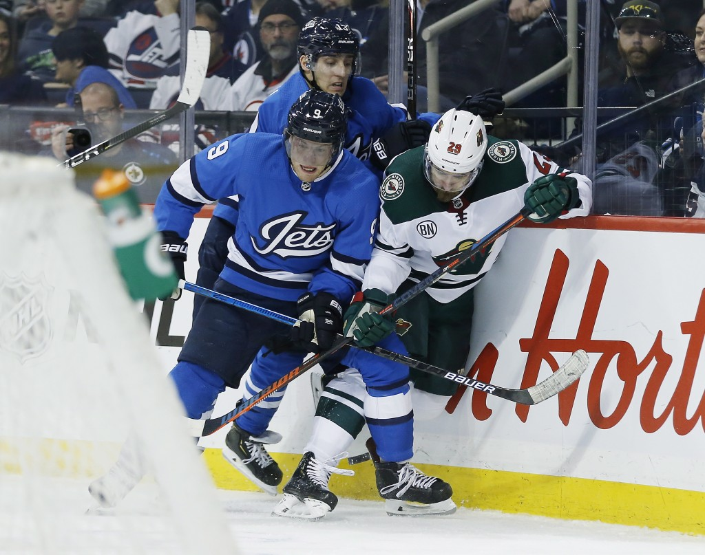Winnipeg Jets' Andrew Copp (9) and Brandon Tanev (13) check Minnesota Wild's Greg Pateryn (29) during second period NHL action in  Winnipeg, Manitoba,...