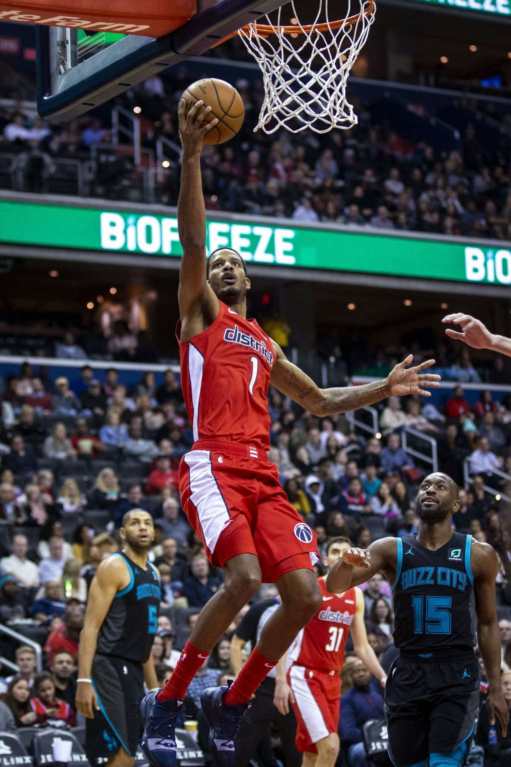 Washington Wizards forward Trevor Ariza (1) attempts a layup past Charlotte Hornets guard Kemba Walker (15) during the second half of an NBA basketbal...