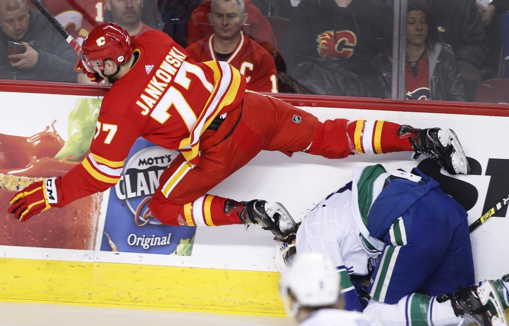 Calgary Flames' Mark Jankowski leaps over Vancouver Canucks' Christopher Tanev during the first period of an NHL hockey game Saturday, Dec. 29, 2018, ...