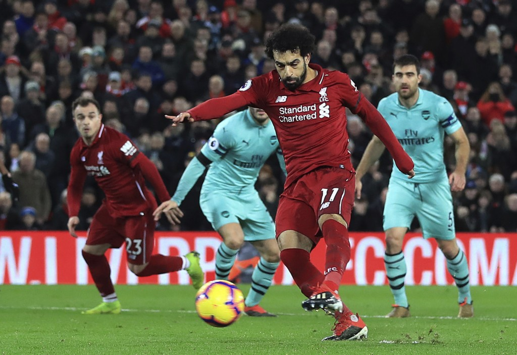 Liverpool's Mohamed Salah scores his side's fourth goal of the game against Arsenal, during their English Premier League soccer match at Anfield Stadi...