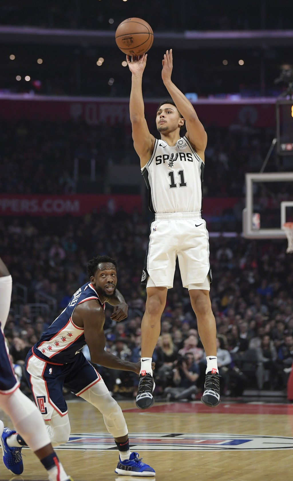 San Antonio Spurs guard Bryn Forbes shoots as Los Angeles Clippers guard Patrick Beverley defends during the first half of an NBA basketball game Satu...