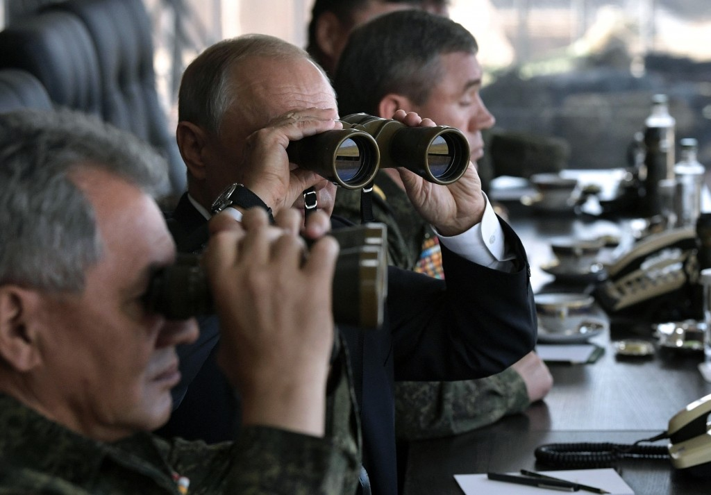 FILE In this file photo taken on Thursday, Sept. 13, 2018, Russian President Vladimir Putin, center, holds binoculars while watching a military exerci...