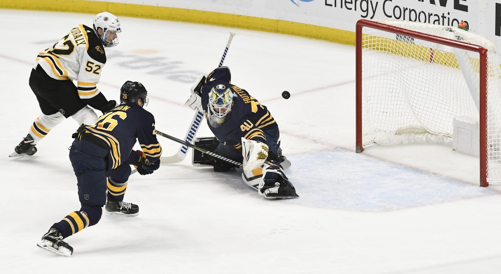 Boston Bruins center Sean Kuraly (52) puts the game-winning goal past Buffalo Sabres goalie Carter Hutton (40) as defenseman Rasmus Dahlin (26) trails...