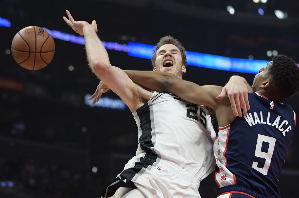 San Antonio Spurs center Jakob Poeltl, left, tries to shoot as Los Angeles Clippers guard Tyrone Wallace defends during the first half of an NBA baske...