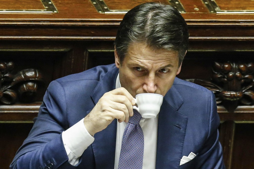 Italian prime minister Giuseppe Conte sips coffee during the vote of confidence on the budget law at the Italian lower chamber in Rome, Saturday, Dec....