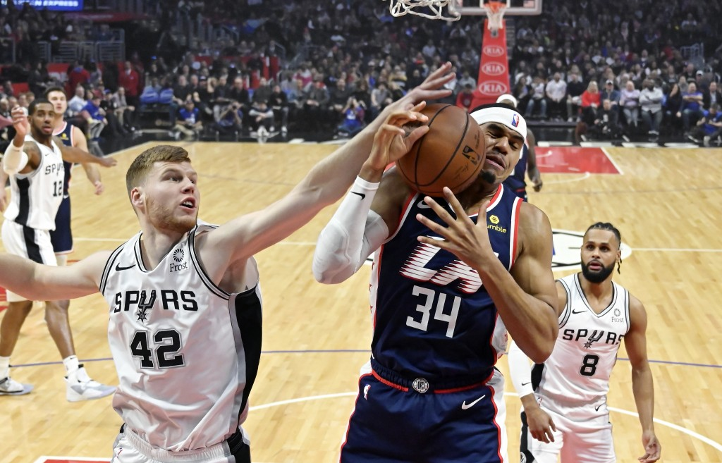 San Antonio Spurs forward Davis Bertans, left, reaches for a rebound as Los Angeles Clippers forward Tobias Harris grabs it while guard Patty Mills, r...