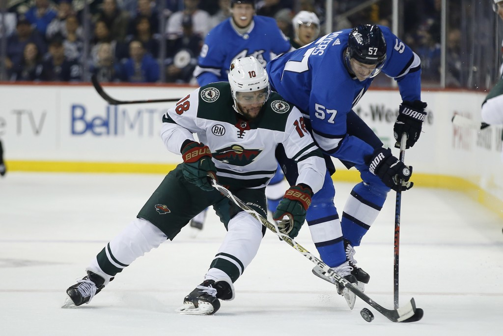 Minnesota Wild's Jordan Greenway (18) steals the puck from Winnipeg Jets' Tyler Myers (57) during first period NHL action in Winnipeg, Manitoba, on Sa...