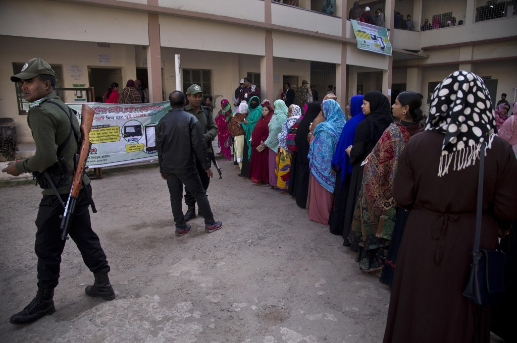 Bangladeshi security personnel stand guard as women line up to cast their votes outside a polling station in Dhaka, Bangladesh, Sunday, Dec. 30, 2018....