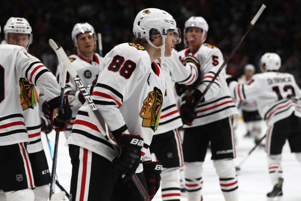 Teammates head to Chicago Blackhawks right wing Patrick Kane (88) after he scored against the Colorado Avalanche in overtime of an NHL hockey game Sat...