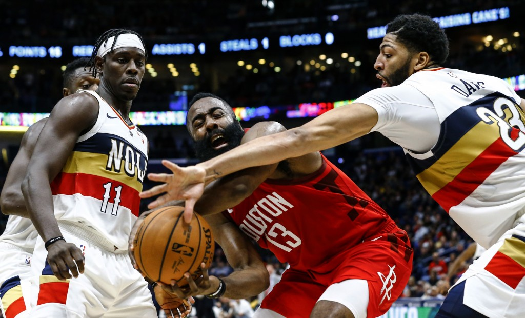 New Orleans Pelicans forward Anthony Davis (23) and guard Jrue Holiday (11) try to steal the ball from Houston Rockets guard James Harden (13) during ...